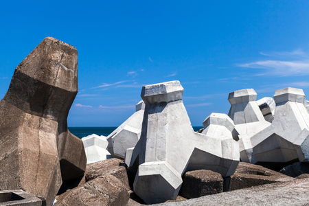 Rough concrete breakwater blocks are under cloudy sky. Industrial background photo