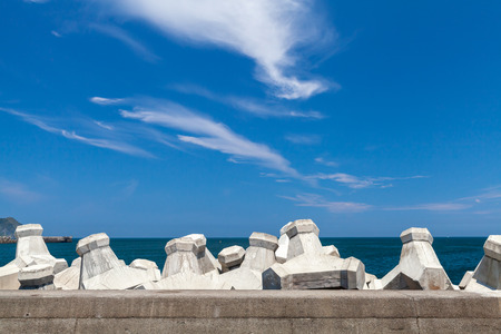 Breakwater structure with concrete blocks under cloudy sky. Industrial background photo