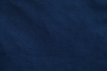 Texture of dark blue fleece, soft napped insulating fabric made from polyester