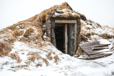 Old cellar with broken door covered with snow. Iceland