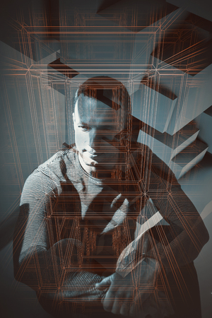 Low key portrait of sitting young adult European man with overlay of wire-frame lines and digital polygonal patterns