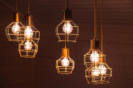 Hangende gloeilampen. Kroonluchter met gele LED-verlichtingselementen bedekt met metalen draadframe lampenkappen, foto met selectieve focus