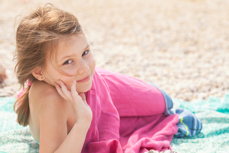 Cute happy smiling Caucasian little girl rests on the beach Zdjęcie Seryjne