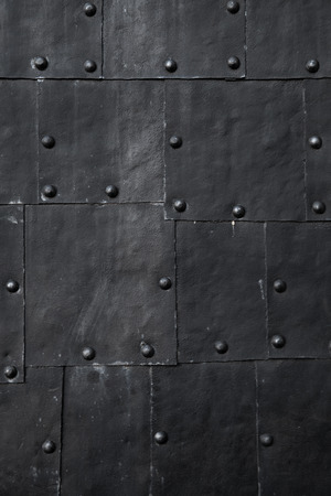 Black submarine hull fragment, grungy metal sheets with rivets, vertical background photo texture Imagens