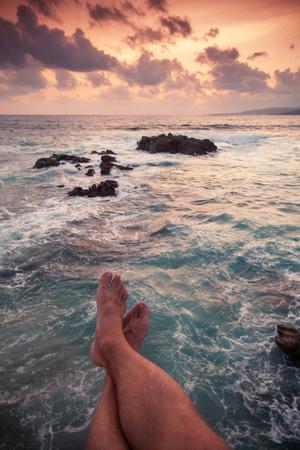 Vertikale Sommerküstenmeerlandschaft bei Sonnenuntergang mit Beinen des entspannenden Mannes am Strand