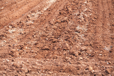 Plowed red soil of an empty field, background photo 版權商用圖片