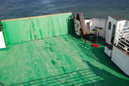 Empty green ferry deck with lifted up loading ramp on bow