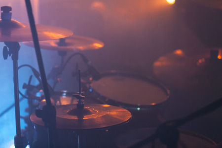 Live music photo background with rock drum set in stage lights. Close-up photo, soft selective focus Foto de archivo