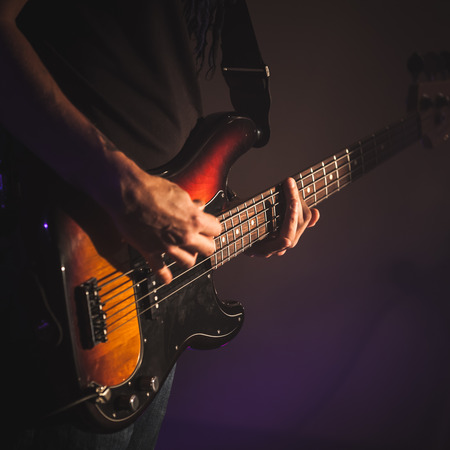 Electric bass guitar player hands, soft selective focus, square live music photo