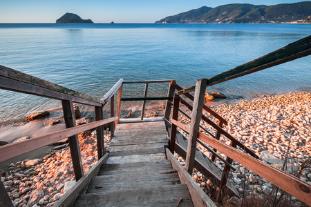 Perspective view of wooden stairs going to beach. Coast of Zakynthos island, Greece