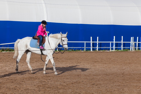 Beginner riding lessons, little girl and white horse are on riding field