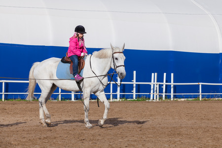 Anfänger-Reitunterricht, kleines Mädchen reitet weißes Pferd auf Reitplatz Standard-Bild