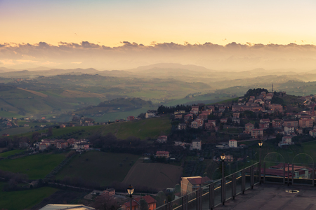 Italian countryside, foggy landscape. Province of Fermo, Italy. Villages and fields on hills are under colorful cloudy sky