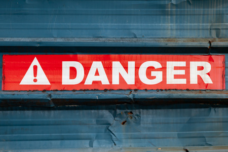 Danger sign on red tape over grungy blue metal wall, close up photo