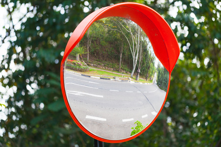 Round mirror in red frame on metal pole at crossing streets for safety Фото со стока