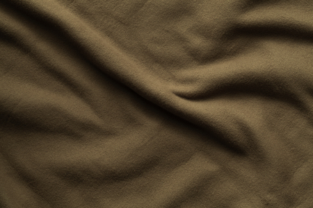 Texture of brown fleece, soft napped insulating fabric made of polyester, wavy pattern, top view