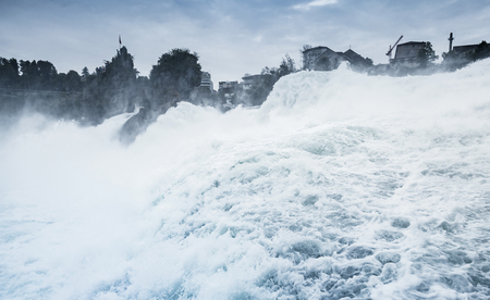 The Rhine Falls blue toned landscape. Fast fallen river water with foam and mist Imagens