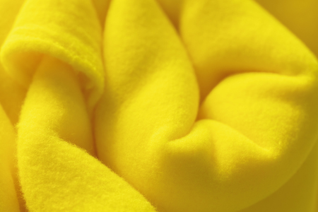 Background with rolled vibrant yellow fleece, soft napped insulating fabric made of polyester