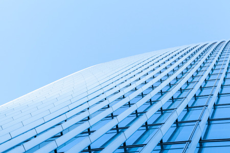Abstract commercial architecture fragment, wall made of metal and shiny glass under blue sky