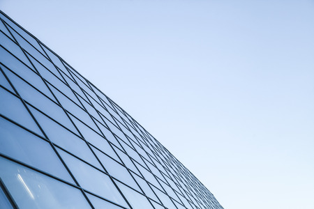 Abstract modern commercial architecture fragment, wall made of steel and shiny glass under blue sky Imagens