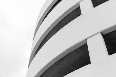 Modern parking lot, round white concrete building exterior, abstract fragment