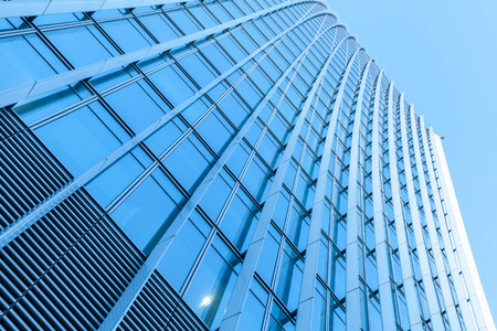 Abstract modern architecture fragment, office building wall made of metal and shiny glass under blue sky