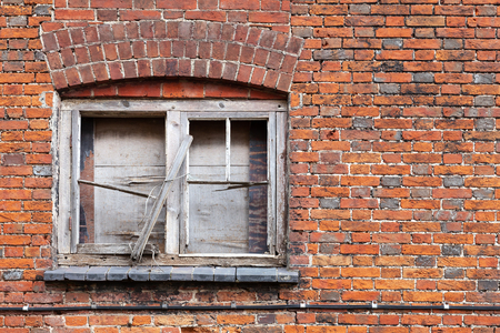 Old locked window with broken wooden frame in grungy brick wall, background photo texture