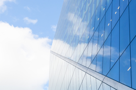 Abstract modern commercial architecture, wall made of metal and shiny glass under blue cloudy sky