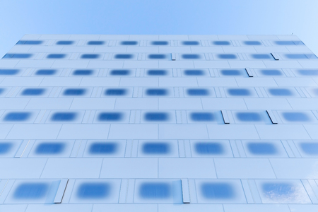 Abstract modern architecture fragment, wall made of steel and toned blue glass with sky reflections