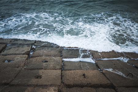 Dark concrete seawall blocks with stormy water, Egypt Alexandria, Egypt Imagens