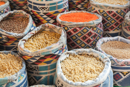 Flour products and grains lie in colorful canvas baskets on the street market in Egypt