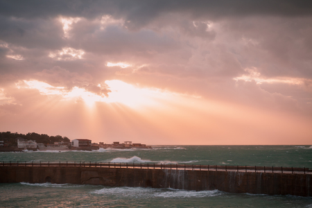 Coastal landscape with big waves on stormy sea water under dramatic evening sky. Alexandria, Egypt