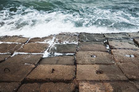 Dark concrete breakwater blocks with stormy seawater, Egypt Alexandria, Egypt