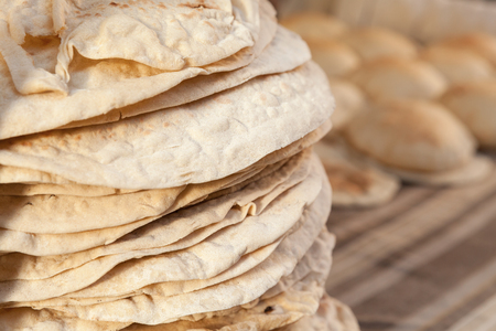 Homemade Kuboos. Stacked traditional pitta bread lie on a counter of street market in Egypt