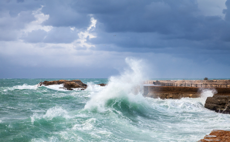 Coastal landscape with big waves on stormy sea water under dark blue cloudy sky. Alexandria, Egypt