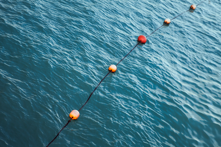 Swimming area border marked with red and orange floating spheres on rope. Alexandria, Egypt Imagens