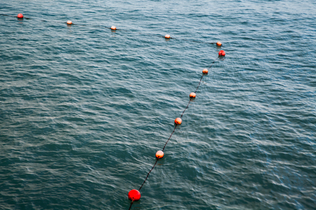 Corner of swimming area marked with red and orange floating spheres on rope. Alexandria, Egypt Imagens