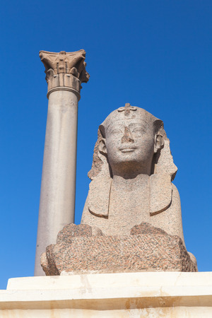 Ancient sphinx and Pompeys Pillar, Alexandria, Egypt. This Roman triumphal column was built in 297 AD