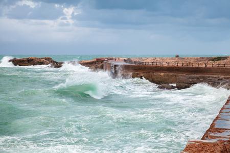 Coastal landscape with waves on stormy sea water under dark blue cloudy sky. Alexandria city, Egypt