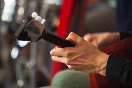 Hands of a man playing balalaika, close-up photo with selective focus