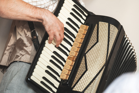 Accordionist plays vintage accordion. Close-up photo with soft selective focus