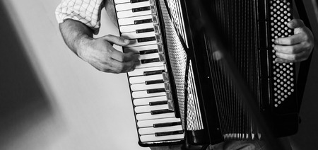 Accordionist plays vintage accordion. Close-up black and white photo with soft selective focus