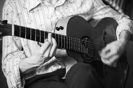 An acoustic guitar player, close-up photo with soft selective focus, black and white Imagens