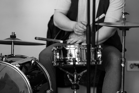 Black and white live music background, drummer plays with drumsticks a drum set. Closeup photo with soft selective focus