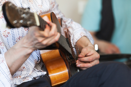 Man playing an acoustic guitar with mediator, close-up photo with selective focus