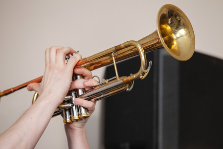 Trumpet in trumpeter hands. It is a brass instrument commonly used in classical and jazz ensembles