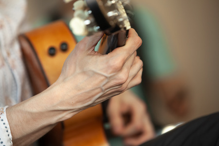 Hands of an acoustic guitar player, close-up photo