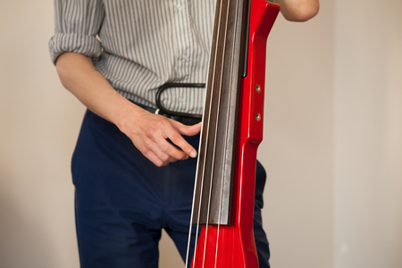 Man plays red modern electric contrabass in musical studio