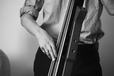 Man plays modern electric contrabass in musical studio, black and white stylized photo
