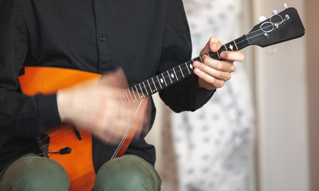 Hands of a man playing balalaika, close-up photo with selective focus and motion blur effect